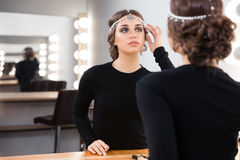 Woman looking at her reflection in the mirror Stock Images