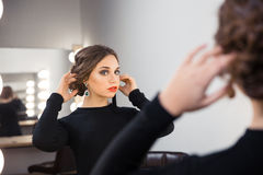 Woman looking at her reflection in the mirror Stock Photo
