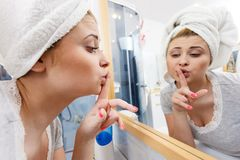 Woman looking at her reflection in mirror. Thinking about her complexes, analyzing face skin complexion showing silence gesture with finger close to mouth Stock Photos