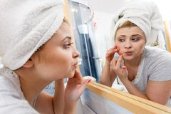 Woman looking in mirror dealing with acne. Woman looking at her reflection in mirror thinking about her complexes having serious face expression, analyzing face Stock Photography