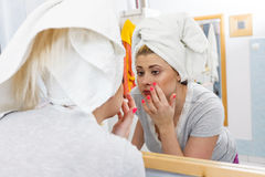 Woman looking at her reflection in mirror Royalty Free Stock Photography