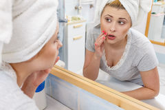 Woman looking at her reflection in mirror. Worried shocked woman looking at her reflection in mirror thinking about her complexes having serious face expression Royalty Free Stock Image