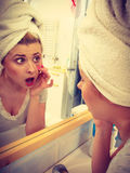 Woman looking at her reflection in mirror Stock Images