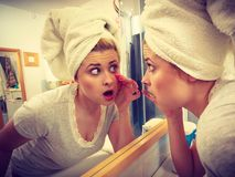 Woman looking at her reflection in mirror. Worried shocked woman looking at her reflection in mirror thinking about her complexes having serious face expression Royalty Free Stock Images