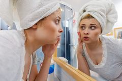Woman looking at her reflection in mirror Royalty Free Stock Photo