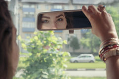 Woman looking at her reflection in the rearview Stock Photo