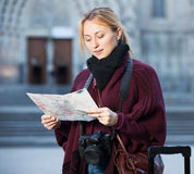 Woman looking for her route. Young cheerful woman having a map and looking for her route in the city Stock Image