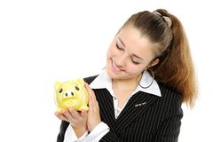 woman looking at her savings in a piggy bank Royalty Free Stock Photos