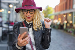 Woman looking at her smartphone in pleasant surprise. Woman looking at her smart phone in pleasant surprise stock image