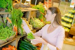 Woman looking at herbs inside store Stock Photo