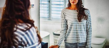Woman looking at herself in the bathroom mirror. At home stock photos