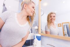 Woman looking at herself in bathroom mirror. Woman with long wet curly hair in bathroom looking in mirror. Blonde girl taking care refreshing her hairstyle in royalty free stock images