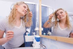 Woman looking at herself in bathroom mirror royalty free stock photos