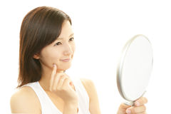 Woman looking at herself in a hand mirror Stock Photos