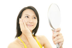 Woman looking at herself in a hand mirror Royalty Free Stock Images