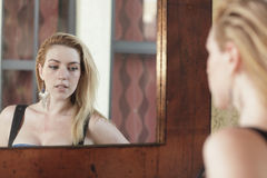 Woman looking at herself in the mirror Royalty Free Stock Images