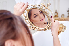 Woman Looking At Herself In The Mirror Stock Photography