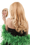 Woman looking herself in mirror. Woman wearing feather boa looking herself in mirror Royalty Free Stock Photos