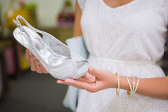 Woman looking at high-heeled sandals Stock Image