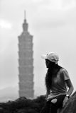 Woman looking at high rise tower Stock Photo