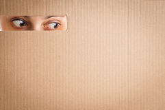 Woman looking through the hole in cardboard Royalty Free Stock Image