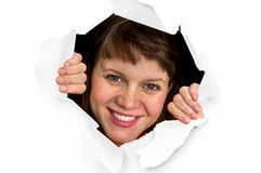 Woman is looking through a hole in torn paper. Beautiful woman is looking through a hole in torn paper Stock Images