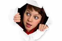 Woman is looking through a hole in torn paper. Beautiful woman is looking through a hole in torn paper Stock Photography