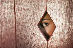 Woman Looking Through a Hole in the Wall Stock Images