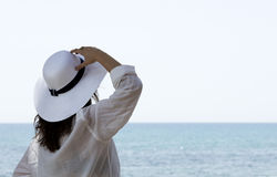 Woman looking the horizon. With a white straw hat Royalty Free Stock Images