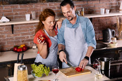 Woman looking how man cutting vegetable Royalty Free Stock Photos
