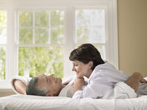 Woman Looking At Husband While Lying In Bed Royalty Free Stock Photos