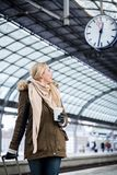 Woman looking at clock in train station as her train has a delay. Woman looking impassionate at clock in train station as her train has a delay Stock Photography
