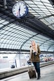 Woman looking at clock in train station as her train has a delay. Woman looking impassionate at clock in train station as her train has a delay Royalty Free Stock Photo