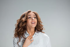 Woman is looking imploring over gray background Royalty Free Stock Photo