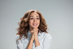 Woman is looking imploring over gray background Royalty Free Stock Photos