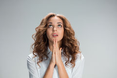 Woman is looking imploring over gray background Royalty Free Stock Photography