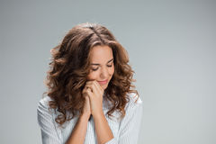Woman is looking imploring over gray background Royalty Free Stock Image