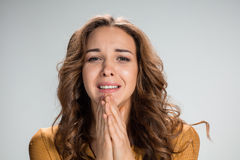 Woman is looking imploring over gray background Stock Image