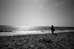 A woman looking at infinite horizon on a sunny day at a seashore. This is a photograph of a woman looking at infinite horizon on a bright sunny day, standing at Royalty Free Stock Image