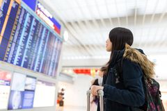 Woman looking at information board and checking her flight Royalty Free Stock Image