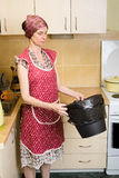 Woman Looking inside a Trash Can. A woman, with a scarf on the head and a red apron, is looking inside a black trash can with a garbage bag, in the kitchen. She stock image