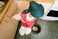 Woman Looking inside a Trash Can. A woman, with a scarf on the head and a red apron, is looking inside a black trash can with a garbage bag, in the kitchen. She stock images