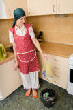 Woman Looking inside a Trash Can. A woman, with a scarf on the head and a red apron, is looking inside a black trash, in the kitchen, holding a garbage bag in royalty free stock photos