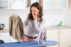 Woman Looking At Iron Burned Cloth Stock Images