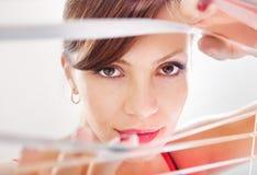 Woman looking through jalousie Royalty Free Stock Image