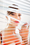 Woman are looking through jalousie l Royalty Free Stock Photos