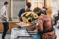 Woman looking at jewelry, holding a bunch of sunflowers purchased at the Columbia Road Flower Market, London, UK Stock Image