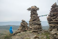 Woman looking at lake Baikal from top of the hillock dedicated to a local Tutelary deity. Siberia, Russia stock images