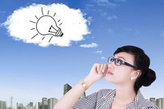 Woman looking at lamp on the cloud Royalty Free Stock Photography