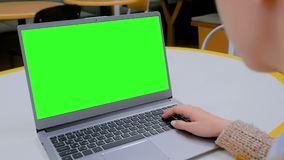 Woman looking at laptop computer with blank green screen in cafe stock video footage